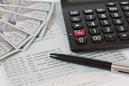 American dollars cash money, calculator and pen on saving account book or financial statement