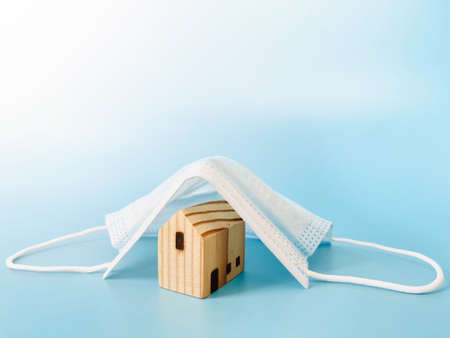Business, finance, real estate, family health protection, stay home,   lockdown or mortgage crisis concept : Wood house model cover by surgical mask with copy space ready for adding or mock up