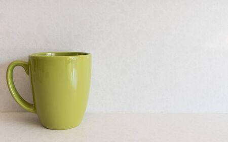 Green coffee mug against a cool white background