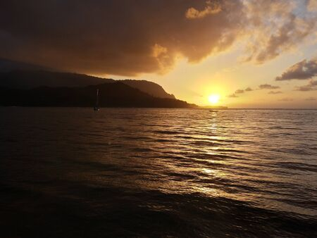 Glowing sunset with dramatic clouds on the waters of Hanalei Bay, Kauai, Hawaii 版權商用圖片