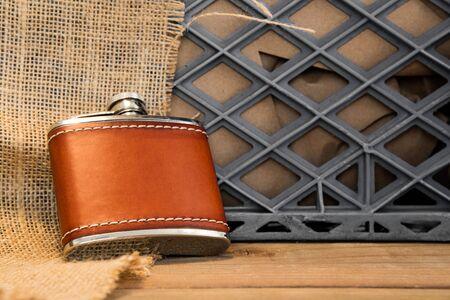 Un frasco de acero inoxidable cubierto de cuero contra una caja de leche y arpillera.