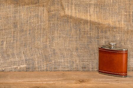 leather wrapped silver flask against a burlap backdrop