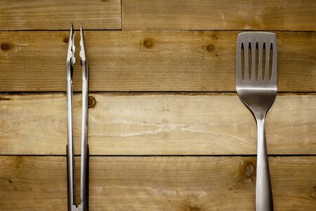 BBQ Spatula and tongs on rustic weathered wood background