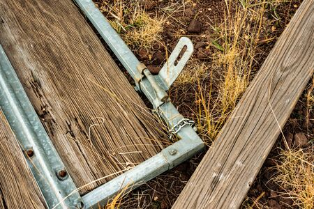 Broken wood gate with metal latch laying on the ground