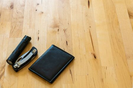 over head shot of male pocket contents flat lay with knife, flash light, and wallet