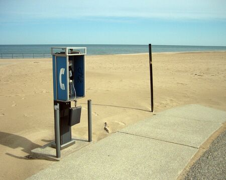 suggests: An unused public payphone on a remote beach - the image suggests technological obsolescence due to cell phones.