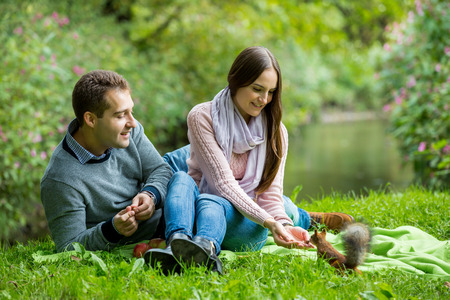 Young beautiful couple having picnic on the lawn in summer park. Woman and man feeding ginger squirrel with nuts in forest. Stock Photo
