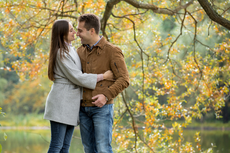 Preview Save to a lightbox Find Similar Images Share Edit Stock Photo: Romantic couple relaxing in autumn park, cuddling, kissing, enjoying fresh air, beautiful nature, nice fall weather. Beloved spending time together. Yellow leaves in background Stock Photo