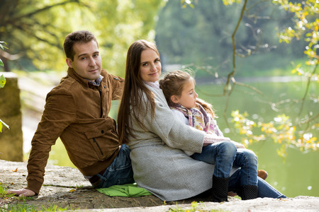 lifestyle looking lovely: Young lovely family sitting at the lake shore in the park and enjoying warm sunny weather. Looking at the camera with sweet smiles. Happy healthy family lifestyle. Stock Photo