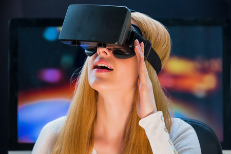 Chica con placer utiliza pantalla montada en la cabeza Foto de archivo - 63719066