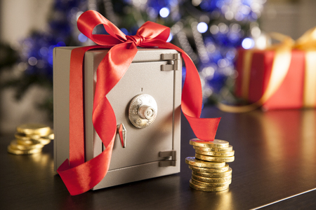 christmas savings: Little safe with red ribbon and golden coins Stock Photo