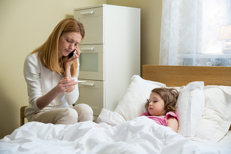 Mother measuring temperature of her ill kid. Sick child with high fever laying in bed and mother holding thermometer. Mother with cell phone calling to doctor Stok Fotoğraf