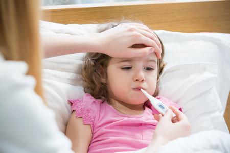 Madre temperatura de su hija enferma de medición. Niño enfermo con fiebre alta tendido en la cama y la madre que sostiene el termómetro. Mano en la frente. Foto de archivo