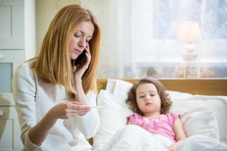 Matka temperaturę swojego chorego dzieciaka pomiaru. Chore dziecko z wysoką gorączką r w łóżku i matka gospodarstwa termometr. Matka z telefonu komórkowego dzwoni do lekarza