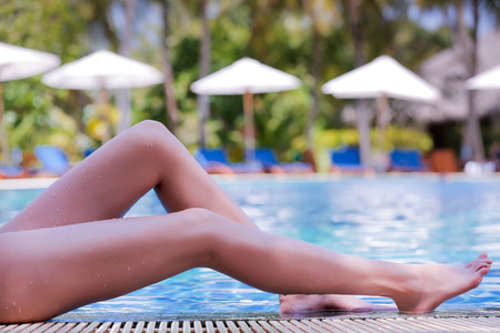 woman foot: Long slim legs with smooth skin on the water edge. Sexy woman in bikini lying and sunbathing on the ledge of the pool. Slim girl with long legs and smooth skin relaxing in the luxury resort. Stock Photo