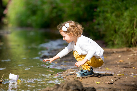 Cute little girl runs a paper boat in the stream in the park. Stretching her hand and reaching the little ship