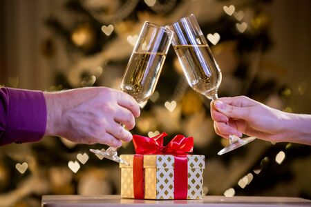 woman's hands: Two glasses of champagne and gift box with red bow. Background with blurred lights, bokeh of heart. Man and woman celebrating