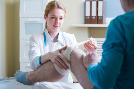 luxacion: Mujeres médico se está rebobinando vendaje de rodilla para el hombre. Médico que atiende a un paciente con trauma de la rótula