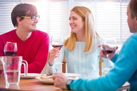 Group Of Young People Enjoying Meal and drinking wine In Restaurant. Friends Dining, celebrating and Hanging out. Hands toasting. Stock Photo