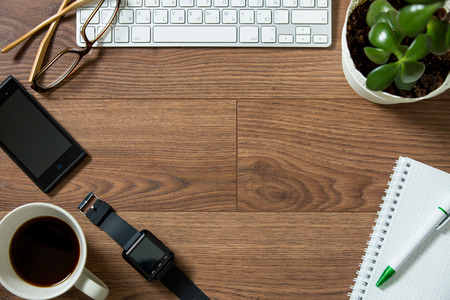 Business workplace from top, flay lay. Keyboard, smart watch, smart phone, glasses, plant, paper notebook, fresh morning coffee on the dark wooden desk Stock Photo