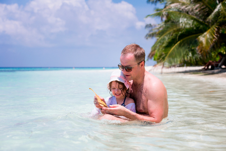 children crab: Happy child playing together with father in blue ocean in a tropical resort. Paradise landscape, turquoise water, coconut palms, white sand. Summer vacations. Family having fun catching crab