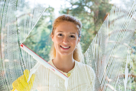 Happy woman in gloves cleaning window with rag and sponge at home. Large window glass in foam. Beautiful view with green forest. Housework concept. Stock Photo