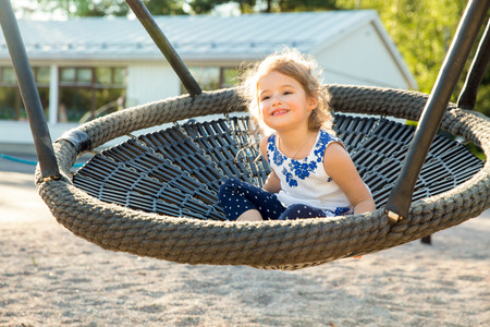 Adorable Little girl laughing happily, riding upside down on a bungee swing on the playground in yellow sunbeams. Happiness, freedom, enjoyment, health. Bright summer day. Banco de Imagens