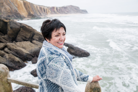short wave: Happy mature attractive woman wrapping herself in warm cardigan on cool ocean coast. Rocks and sea line. Autumn beach. Adult healthy lifestyle.