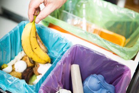 Man putting banana peel in recycling bio bin in the kitchen. Person in the house kitchen separating waste. Different trash can with colorful garbage bags.