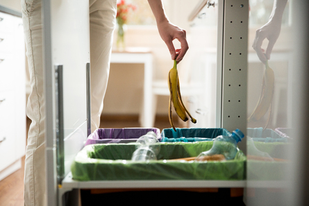 Woman putting banana peel in recycling bio bin in the kitchen. Person in the house kitchen separating waste. Different trash can with colorful garbage bags. Stok Fotoğraf