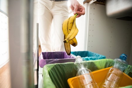 Woman putting banana peel in recycling bio bin in the kitchen. Person in the house kitchen separating waste. Different trash can with colorful garbage bags. Archivio Fotografico