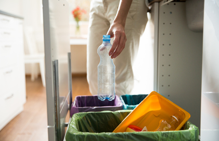 Man putting empty plastic bottle in recycling bin in the kitchen. Person in the house kitchen separating waste. Different trash can with colorful garbage bags. Stock Photo