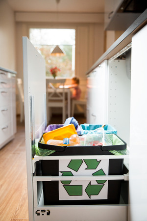 segregated: Three trash bins with sorted garbage in kitchen cabinet with segregated household garbage - plastic, cardboard and bio cans. Ecology and recycle concept. Recycling sign. Girl sitting at the table