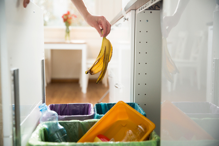Woman putting banana peel in recycling bio bin in the kitchen. Person in the house kitchen separating waste. Different trash can with colorful garbage bags. Banco de Imagens