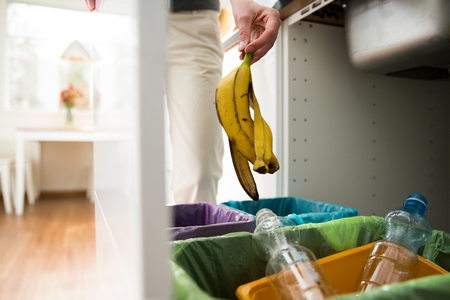 Woman putting banana peel in recycling bio bin in the kitchen. Person in the house kitchen separating waste. Different trash can with colorful garbage bags. Reklamní fotografie
