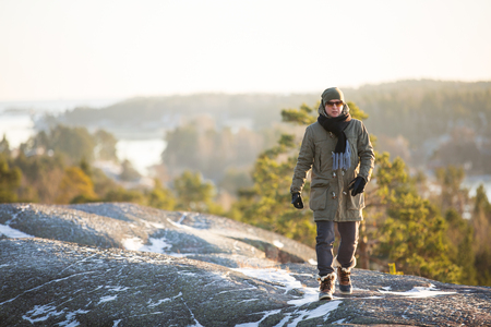 winter finland: Finland, Helsinki, late autumn. Baltic sea, bay. Still water of the gulf, islands with forests. Low winter sun, dusk, pine trees on rock. Scenic Finnish landscape. Man standing on top of the rock