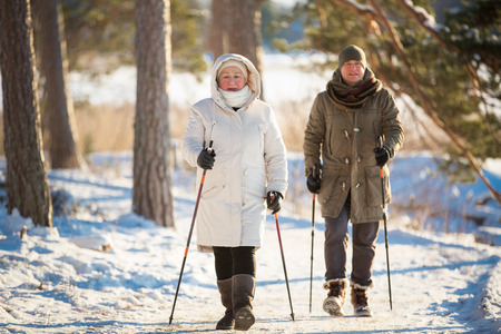 Winter sport in Finland - nordic walking. Senior woman and man hiking in cold forest. Active people outdoors. Scenic peaceful Finnish landscape.