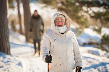 フィンランドのノルディック ・ ウォーキングの冬スポーツ。年配の女性と男性の冷たい森のハイキングします。屋外活動的な人。風光明媚な静かな