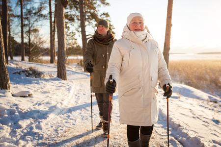 Zima sport w Finlandii - nordic walking. Starszy kobieta i mężczyzna turystyka w zimnym lesie. Aktywnych ludzi na zewnątrz. Scenic spokojna fińskiego krajobrazu. Zdjęcie Seryjne
