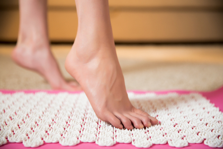 Female feet standing on acupressure mat. Self acupuncture massage. Woman having alternative medicine treatment. Фото со стока