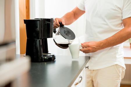 台所の男はガラスのポットから熱い濾過コーヒーのマグカップを注ぎます。午前中に朝食をとる 写真素材