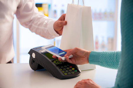 Wireless payment using smartphone and NFC technology. Close up. Customer paying with smart phone in pharmacy. Close Up shopping Stock Photo