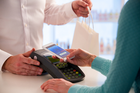 Wireless payment using smartphone and NFC technology. Close up. Customer paying with smart phone in pharmacy. Close Up shopping Archivio Fotografico