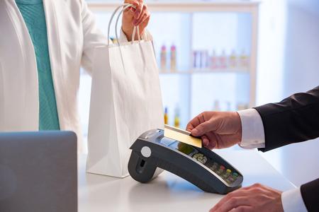 Cliente pagando con tarjeta sin contacto. Tecnología de pago NFC en tienda. De cerca. Compras en farmacia.