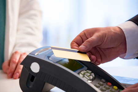 Customer paying with contactless card. NFC technology payment in store. Close Up. Shopping in pharmacy. Stock Photo