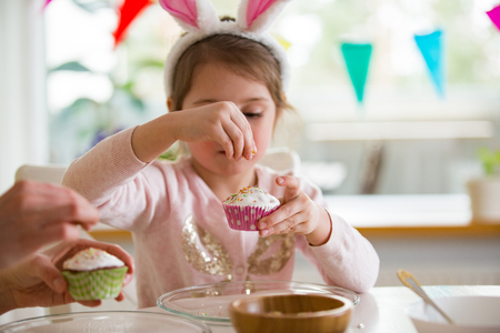 Mother and daughter celebrating Easter, cooking cupcakes, covering with glaze. Happy family holiday. Cute little girl in bunny ears. 版權商用圖片