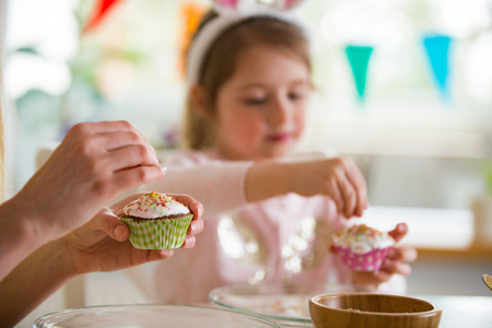 Mother and daughter celebrating Easter, cooking cupcakes, covering with glaze. Happy family holiday. Cute little girl in bunny ears. Banco de Imagens