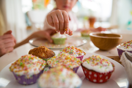 Mother and daughter celebrating Easter, cooking cupcakes, covering with glaze. Happy family holiday. close-up childs hands
