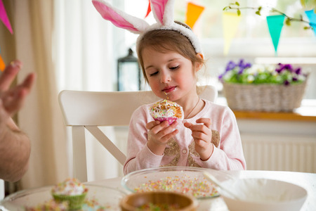 Father and daughter celebrating Easter, eating cupcakes covered with glaze. Happy family holiday. Cute little girl in bunny ears. Beautifully decorated room