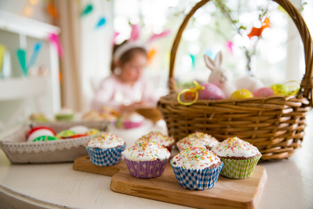 Easter celebration, close-up table with glazed cupcakes, basket with Easter eggs and bunny. Happy family holiday Stock Photo